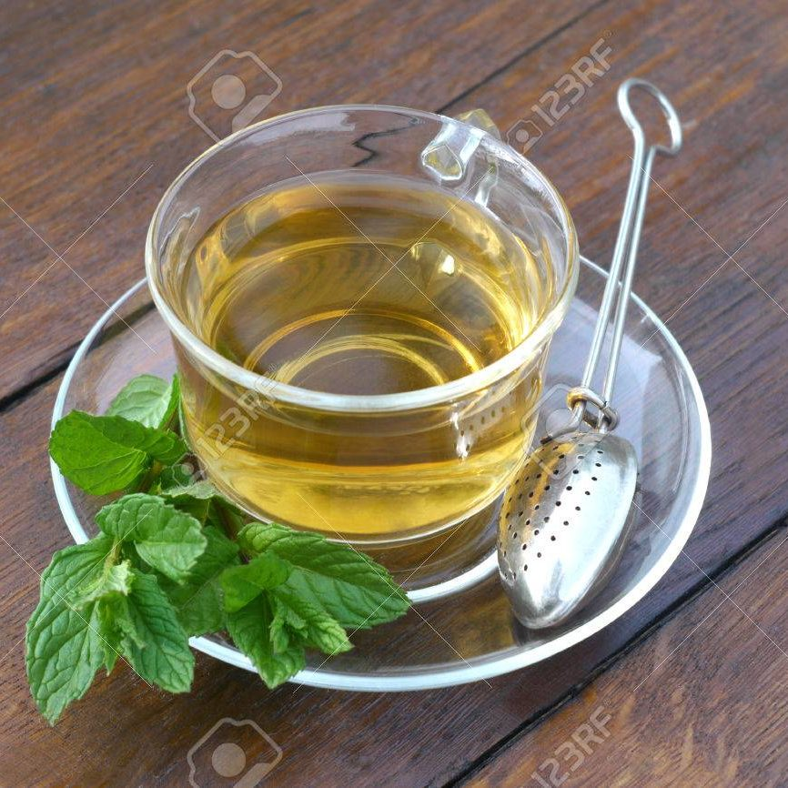 Glass cup of mint tea with mint leaves and tea holder spoon, served outside on a wooden desk